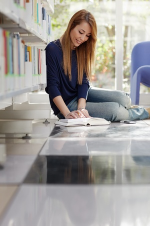 female college student sitting on floor in library, reading book and taking notes. Vertical shape, full length, side view, copy space Stock Photo - 9367031