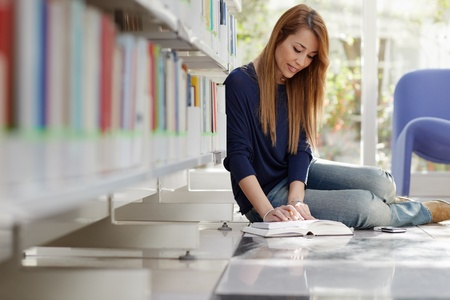 female college student sitting on floor in library, reading book and taking notes. Horizontal shape, full length, side view photo