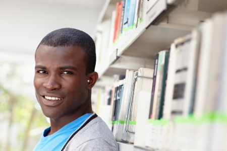 african american male college student leaning on shelf in library and looking at camera. Horizontal shape, head and shoulders, copy space Stock Photo - 9481610