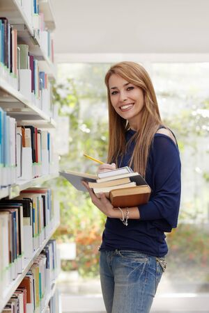 waist up: female blonde college student taking book from shelf in library and looking at camera. Vertical shape, side view, waist up Stock Photo