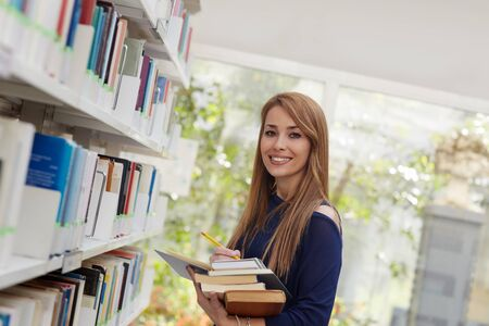 waist up: female blonde college student taking book from shelf in library and looking at camera. Horizontal shape, side view, waist up