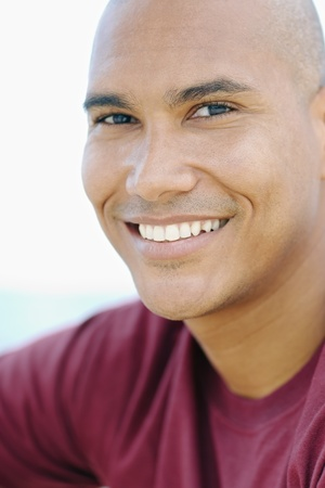 portrait of young hispanic guy with shaved head looking at camera near the sea. Vertical shape, head and shoulders Stock Photo - 9481612
