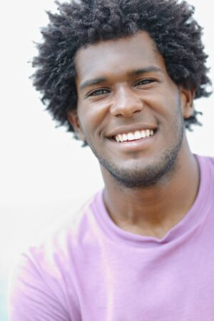 portrait of young african american guy looking at camera near the sea. Vertical shape, head and shoulders