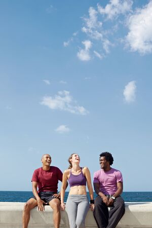 caucasian, hispanic and african american friends smiling and having fun near the sea. Vertical shape, three quarter length, copy space Stock Photo - 9481620