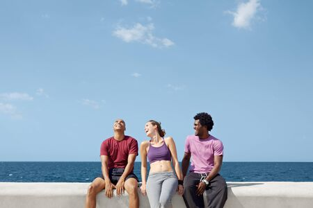 caucasian, hispanic and african american friends smiling and having fun near the sea. Horizontal shape, three quarter length, copy space Stock Photo - 9517852