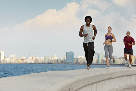 active holiday: Group of young people running along the Caribbean sea in Havana, Cuba. Horizontal shape, full length, copy space