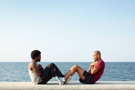 sit shape: young african american man and hispanic friend doing series of sit-ups along the Caribbean sea in Havana, Cuba. Horizontal shape, full length, side view, copy space Stock Photo