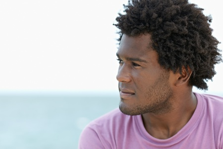 contemplation: portrait of young african american guy looking away near the sea. Horizontal shape; head and shoulders; copy space