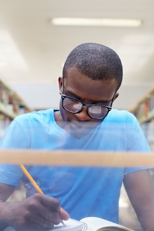african american male college student sitting at desk in library and reading book. Reflections of paperwork on eyeglasses. Vertical shape, front view Stock Photo - 9533797
