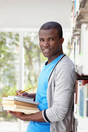 african american male college student leaning on shelf in library and looking at camera. Vertical shape, waist up, front view Stock Photo - 9533790