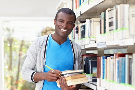 waist up: african american male college student leaning on shelf in library and looking at camera. Horizontal shape, waist up, front view Stock Photo