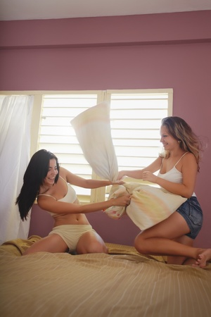 pillow fight: two caucasian female friends playing pillow fight in bedroom. Vertical shape, side view, full length, copy space
