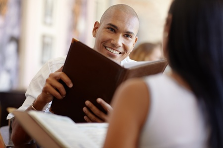 young adult hispanic couple dining out in restaurant and reading menu. Horizontal shape, waist up, focus on background