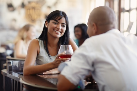 young adult hispanic couple dining out in restaurant and toasting with cocktails. Horizontal shape, front view, focus on background photo
