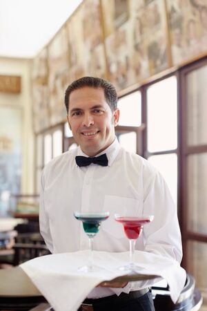 serving tray: hispanic waiter serving adult couple at table in restaurant and looking at camera. Horizontal shape, front view, waist up