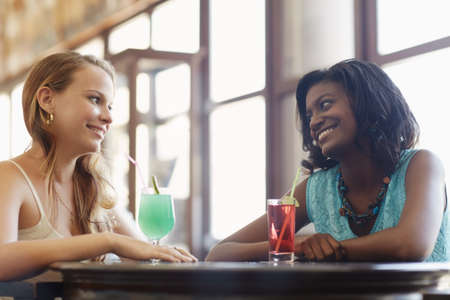 african and latin american female friends drinking cocktails and talking in a pub. Horizontal shape, side view, waist up photo