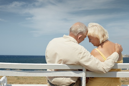 serene people: senior caucasian couple sitting on bench near the sea and hugging. Horizontal shape, rear view, copy space