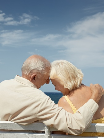 senior caucasian couple sitting on bench near the sea and hugging. Vertical shape, rear view, copy space photo