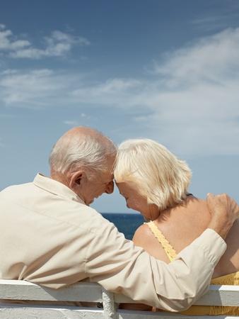 senior Kaukasische paar zittend op een bankje in de buurt van de zee en knuffelen. Verticale vorm, achteraanzicht, kopie ruimte