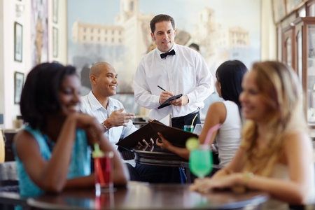 dining out: young adult hispanic couple dining out in restaurant and talking to waiter in bow tie. Horizontal shape, front view, waist up Stock Photo