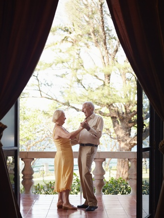 female senior adults: senior caucasian couple on vacation, dancing on terrace in hotel. Vertical shape, full length, side view