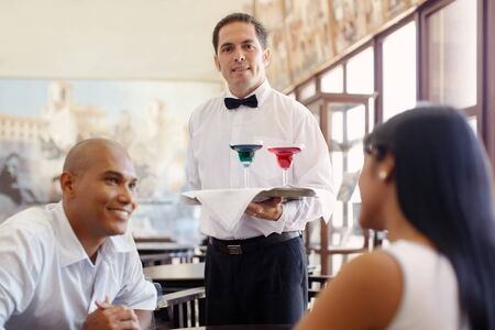 číšník: hispanic waiter serving adult couple at table in restaurant and looking at camera. Horizontal shape, front view, waist up