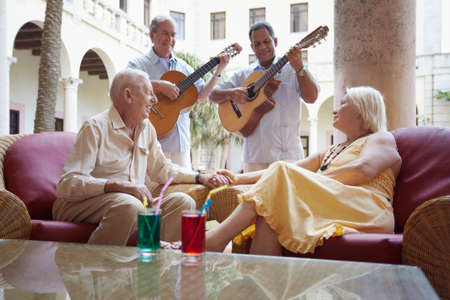 senior caucasian couple sitting in bar at hotel and listening to musicians playing guitar. Horizontal shape photo