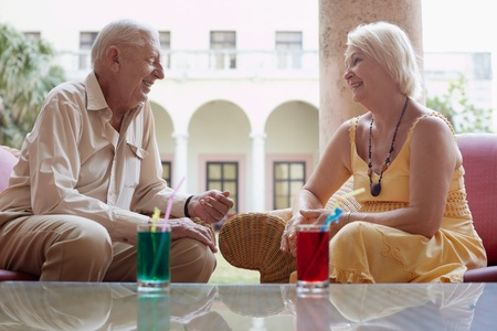 senior caucasian couple sitting in bar at hotel with cocktails and talking. Horizontal shape, side view Stock Photo - 9626338