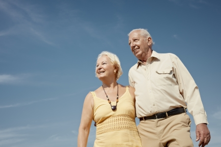 senior caucasian couple walking on sunny day and hugging. Horizontal shape, low angle view, copy space photo