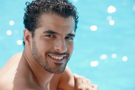 Feliz jóvenes hispano guapo sonriente y relajantes cerca de piscina del hotel. Forma horizontal, cabeza y hombros, espacio de copia