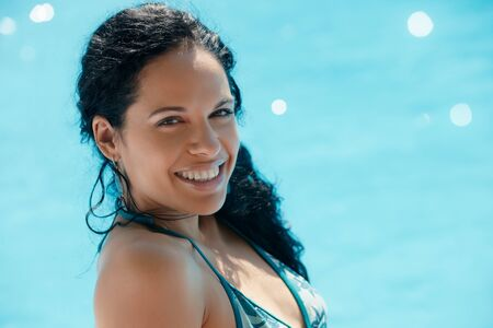 Beautiful happy young hispanic woman smiling and relaxing near resort swimming pool. Horizontal shape, side view, copy space photo
