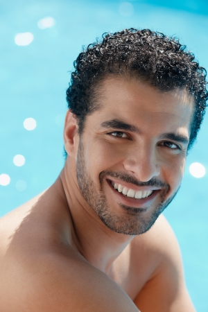 look latino: Handsome happy young hispanic man smiling and relaxing near hotel pool. Vertical shape, head and shoulders