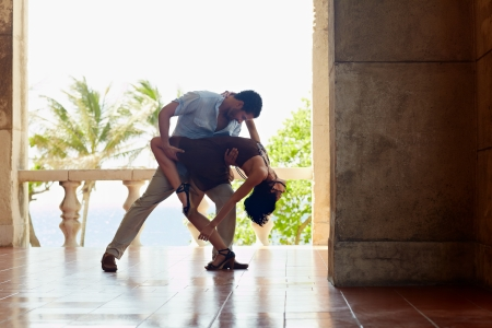 salsa dance: young hispanic couple dancing latin american dance outdoors. Horizontal shape, side view, full length