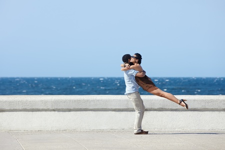 near side: euphoric young couple meeting and hugging near the sea. Horizontal shape, side view, copy space