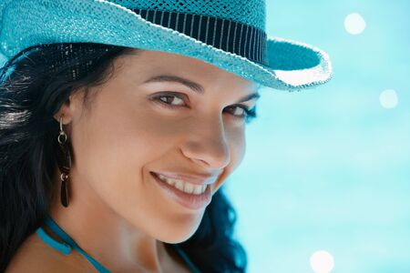 Beautiful happy young hispanic woman in straw hat smiling and relaxing near hotel pool. Horizontal shape, head and shoulders, copy space Stock Photo - 9663705