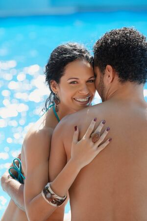 Honeymoon: happy young newlyweds smiling and relaxing near hotel pool. Vertical shape, waist up, copy space Stock Photo - 9663708