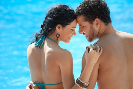 Honeymoon: happy young newlyweds smiling and relaxing near hotel pool. Horizontal shape, rear view, copy space  photo