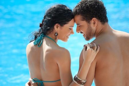 bikini couple: Honeymoon: happy young newlyweds smiling and relaxing near hotel pool. Horizontal shape, rear view, copy space