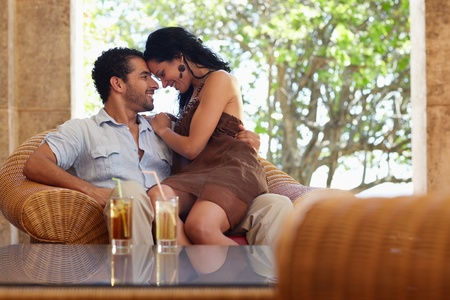 caress: honeymoon: young just married hispanic couple sitting on armchair in hotel bar and hugging. Horizontal shape
