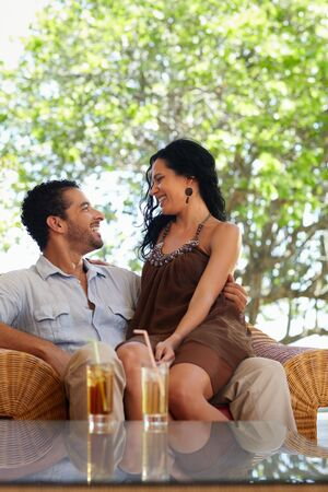honeymoon: young just married hispanic couple sitting on armchair in hotel bar. Vertical shape, copy space photo