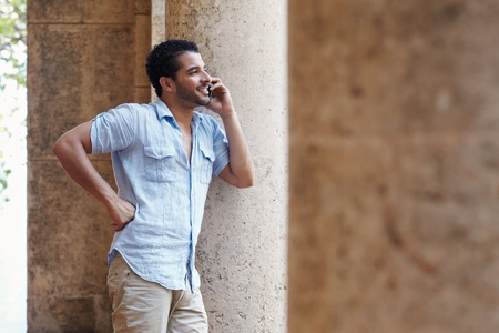 mid adult hispanic man talking on mobile phone and leaning on columns outdoors. Horizontal shape, side view, copy space photo