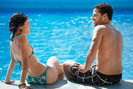 newlyweds: Honeymoon: happy young newlyweds smiling and relaxing near hotel pool. Horizontal shape, rear view, copy space