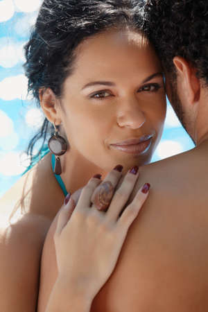 look latino: Honeymoon: happy young newlyweds smiling and relaxing near hotel pool. Vertical shape, head and shoulders