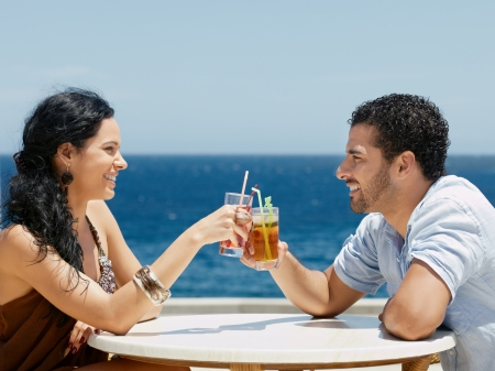 near side: honeymoon: young just married hispanic couple sitting at bar table near the sea and drinking cocktail. Horizontal shape, side view, copy space Stock Photo