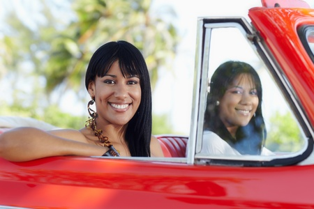 young adult brunette twin women driving convertible red car and looking at camera. Horizontal shape, side view Stock Photo - 9749776
