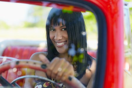 young adult brunette woman driving convertible red car and looking at camera. Horizontal shape, front view Stock Photo - 9749784