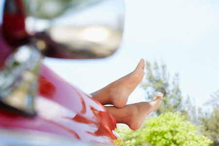 young adult woman relaxing with feet out of convertible red car. Horizontal shape, side view, copy space