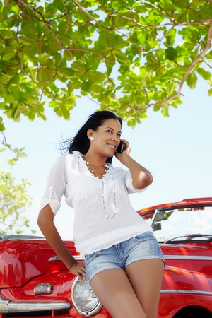cabrio: young adult brunette woman leaning on convertible red car and talking on mobile phone. Vertical shape, front view, three quarter length