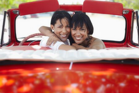 over shoulders: young adult brunette twin women driving convertible red car and looking over shoulders. Horizontal shape, rear view, copy space Stock Photo