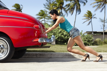 broken car: young hispanic woman pushing broken down red convertible vintage car. Horizontal shape, full length, side view Stock Photo